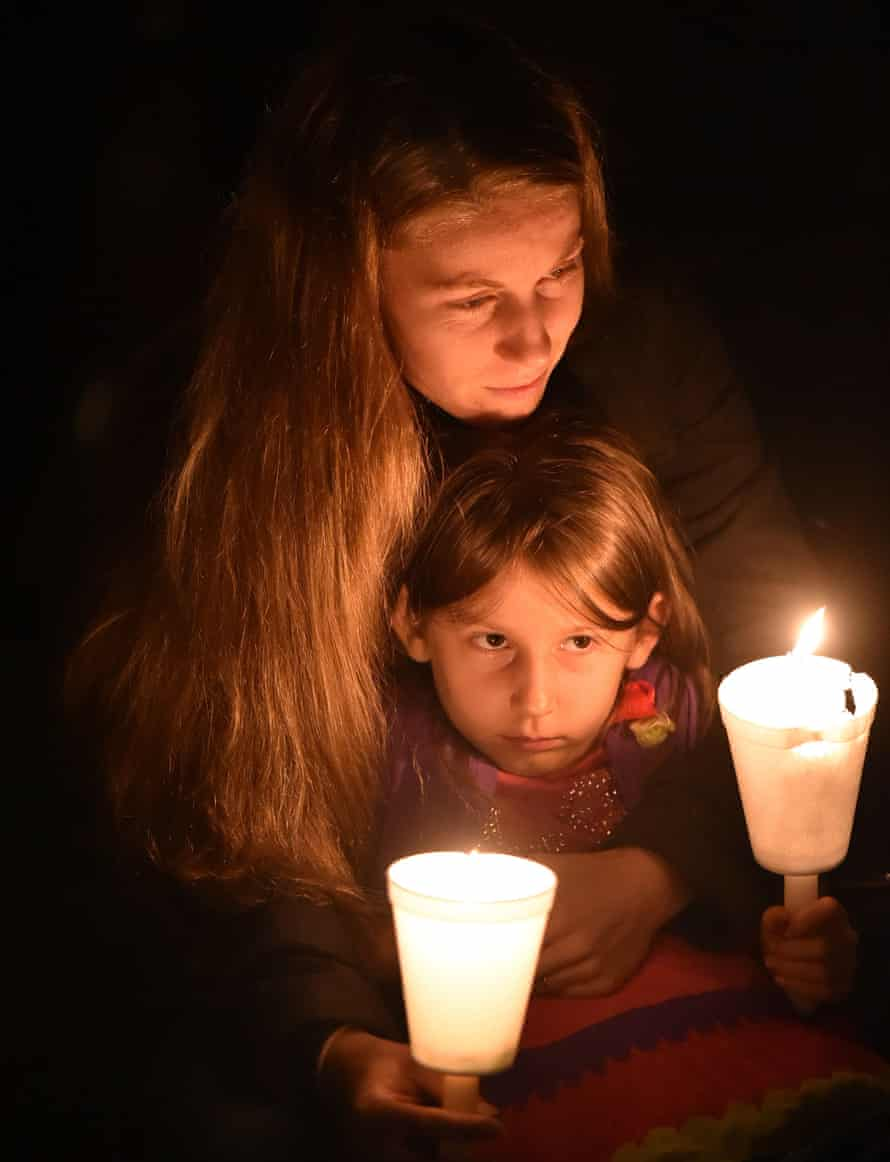 A woman holds her daughter during a vigil in Roseburg, Oregon for ten people killed and seven others wounded in a shooting at a community college.