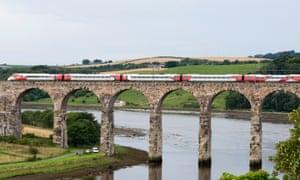 A Virgin train crosses the Royal Border bridge, travelling south from Scotland.