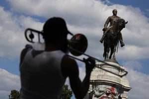 A musician plays trombone near the statue of Robert E Lee on Monument Avenue in Richmond before its removal.