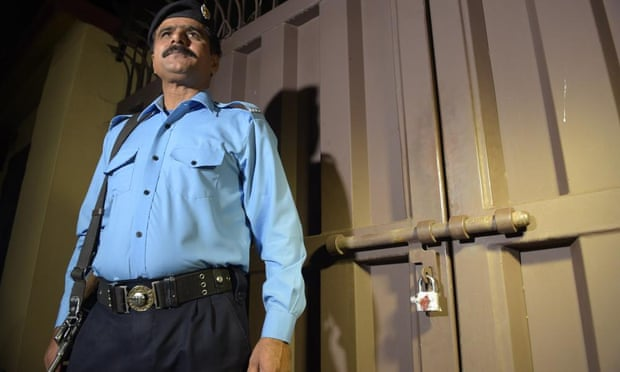 A Pakistani policeman stands guard outside the office of the international charity 'Save the Children' sealed by order of Pakistani authorities in Islamabad.