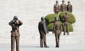 A North Korean soldier looks through binoculars towards the border village of Panmunjom in Paju, South Korea