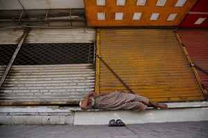A man sleeps outside a closed market stand during a lockdown in Karachi, Pakistan