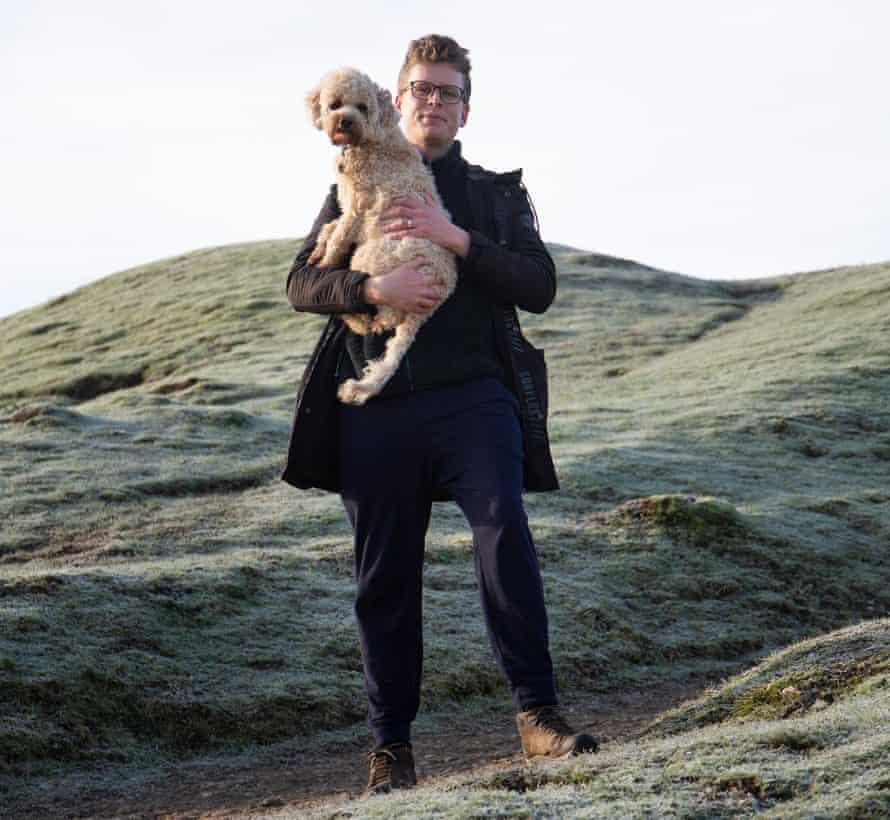 Walk James, holding his dog, at Cissbury Ring, South Downs