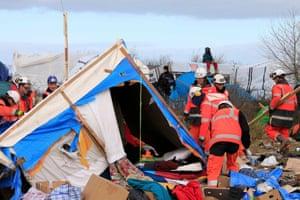 Calais, France: A man sits on a makeshift shelter