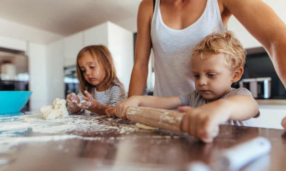 Little boy with his mother and sister preparing dough with rolling pin on kitchen table