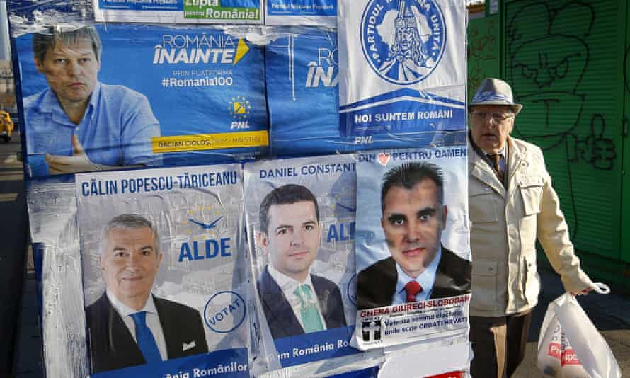 A Romanian man walks past election posters in Bucharest before this Sunday's election