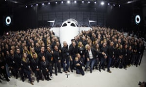Sir Richard Branson poses with employees in front of Virgin Galactic's new spaceship.