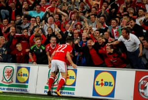 Wales' Ben Woodburn celebrates scoring their first goal with fans.