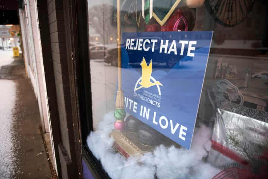 """The 12,000 person town of Baraboo, Wis. has become the focus of international attention for a photo of high school boys making what appears to be a Nazi salute after the image went viral. The community has held town meetings to address the issue and handed out signs like this one, seen in a storefront on 4th Ave. downtown Dec. 31, 2018, that says """"Reject Hate, Unite in Love."""" Photo by Lauren Justice"""