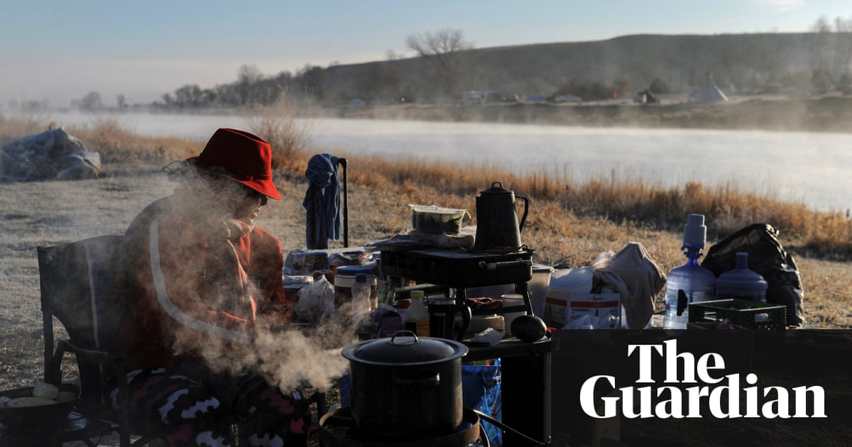 a woman sits by a fire during a protest against the dakota access pipeline the