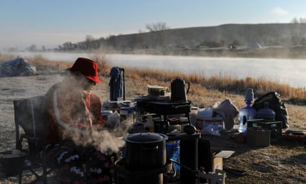 A woman sits by a fire during a protest against the Dakota Access pipeline. The company says it will not halt construction, despite requests by federal agencies to delay the project.