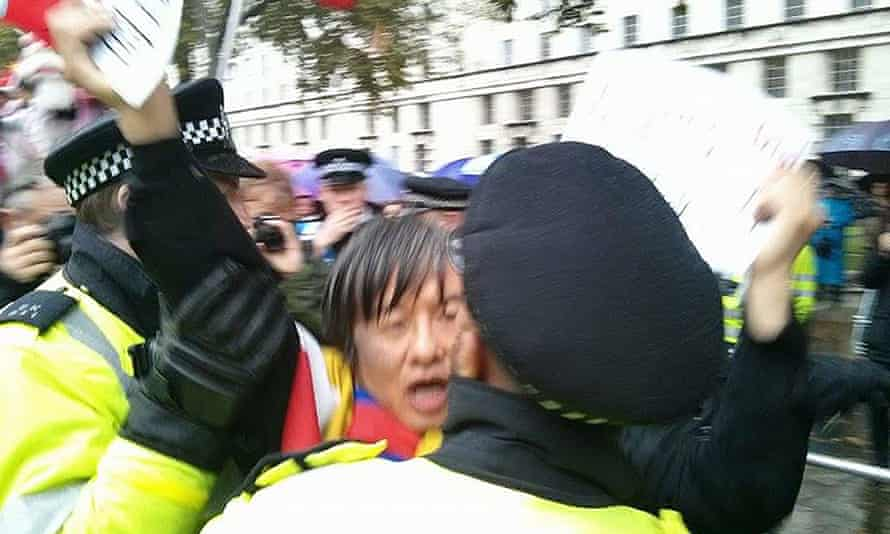 Shao Jiang, 47, grabbed by police officers while protesting outside Mansion House, London shortly before Xi Jinping arrived at the venue.