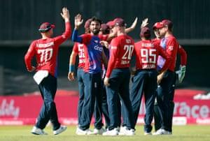 Saqib Mahmood celebrates with teammates after taking the wicket of Babar Azam.