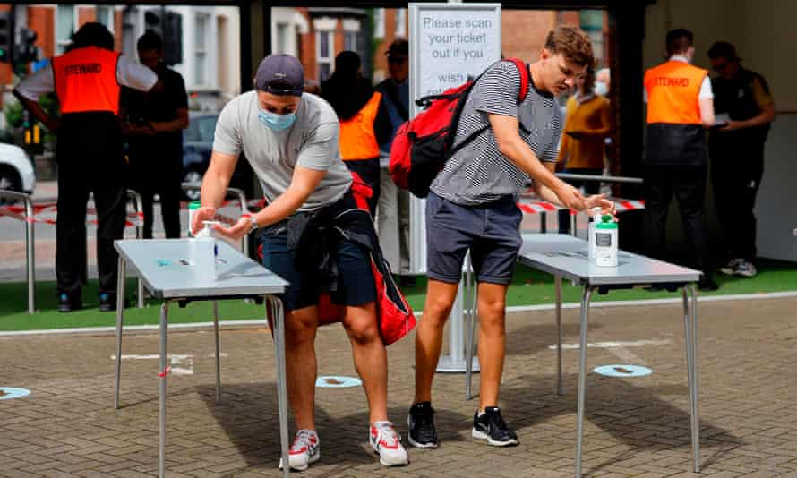 Spectators sanitise their hands as they arrive at the Oval.