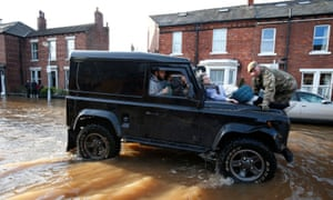 Margaret McCraken, 79, is helped from her home in Broad Street in Carlisle through the floods by members of the armed forces who have been called in to help evacuate people