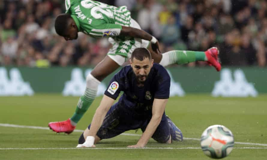 Real Madrid's Karim Benzema sees the ball evade him after a tussle with Real Betis' Emerson.