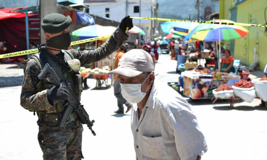 An elderly man is granted entry to the market by a masked armed soldier in Nebaj