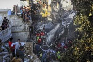 Volunteers look for survivors of a plane that crashed in a residential area of Karachi.