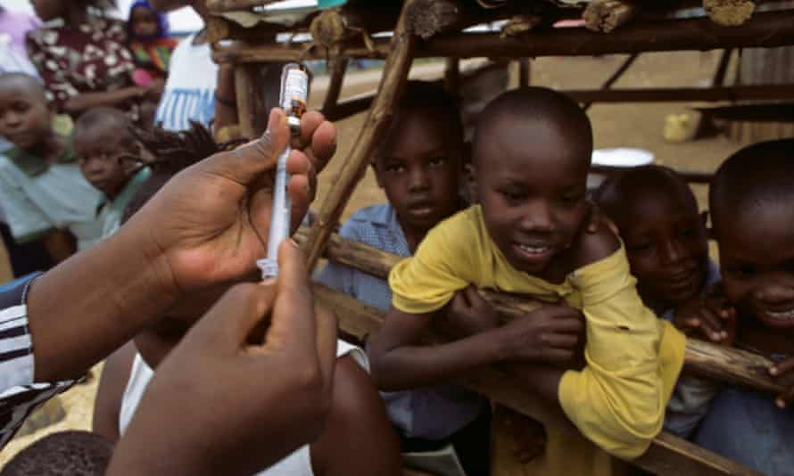 Kenyan school children wait to be given their measles vaccine