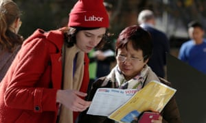 A pre-poll voter seeks guidance from a Labor party volunteer before completing her ballot at a polling centre at Sydney's Town Hall.