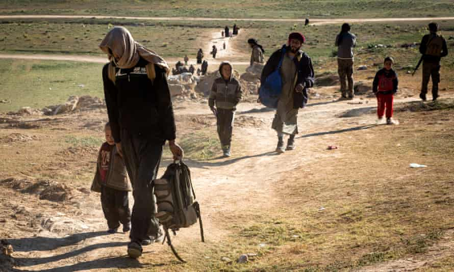 Civilians who fled the fighting in the city of Baghuz arrive at a screening point in Syria
