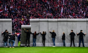 Volunteers assemble a replica Berlin Wall on the halfway line, which was then pulled down before kicked off.