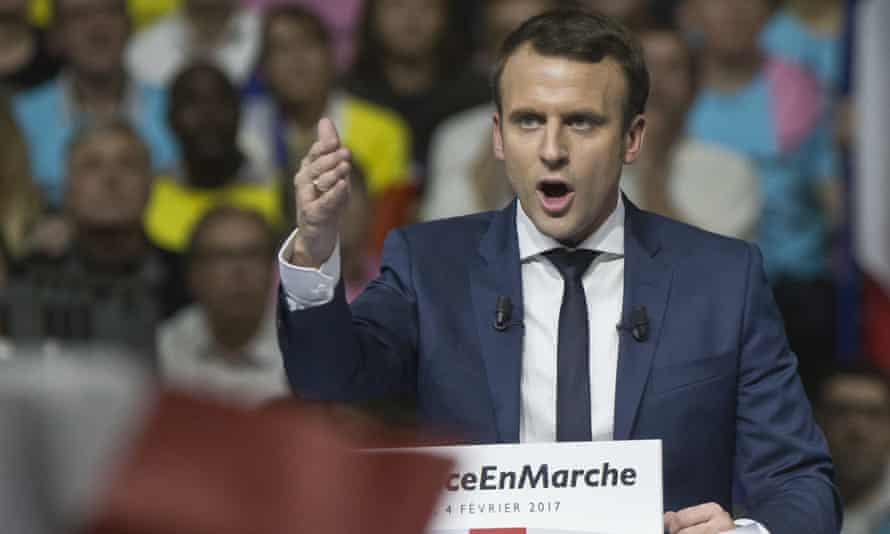 Supporters of Presidential candidate Emmanuel Macron holds placards as he speaks during a meeting in Lyon, central France.