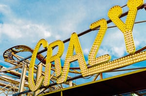 """Stock photo of the word """"CRAZY"""" in lights as the signage for a roller coaster on the Brighton Pier in Sussex, England."""