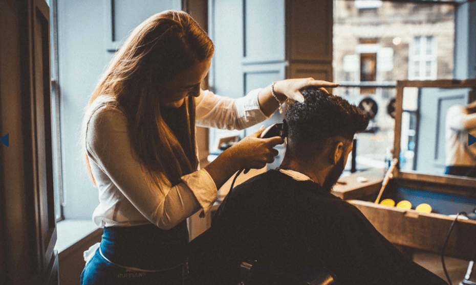 A man sitting in a salon and a woman barber shaving the back of his hair