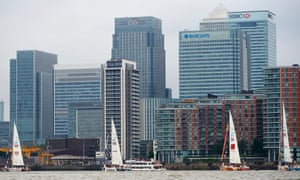 Yachts sail past London's financial district at Canary Wharf