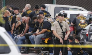 A McLennan County deputy stands guard near a group of bikers in the parking lot of a Twin Peaks restaurant on Sunday.