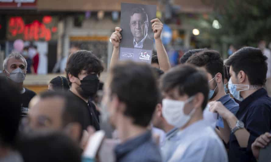 A supporter of presidential election candidate Abdolnaser Hemmati holds up a poster at an election campaign in Tehran.