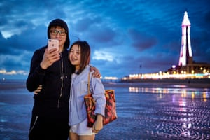 Charlie Wen from Malaysia and Lan Yi Qin from China take pictures of themselves on the beach, lit by the glow of the illuminations