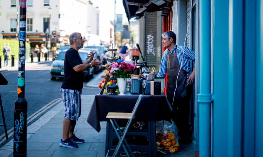 A customer chats to a shop owner in Portobello market in west London.