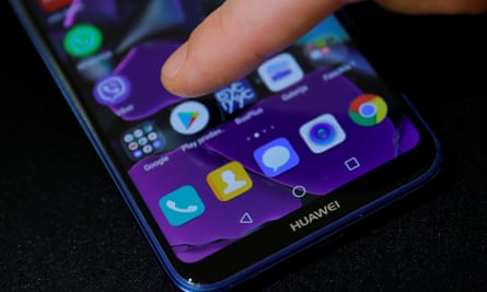 Man points a finger to the Google Play app logo on his Huawei smartphone