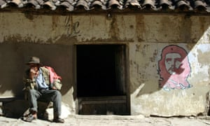 A man sits outside a house next to the image of Che Guevara in La Higuera, Bolivia.