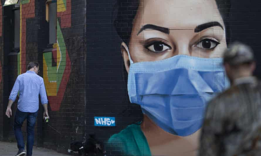 A man walks past a piece of street art depicting an NHS nurse wearing a face mask