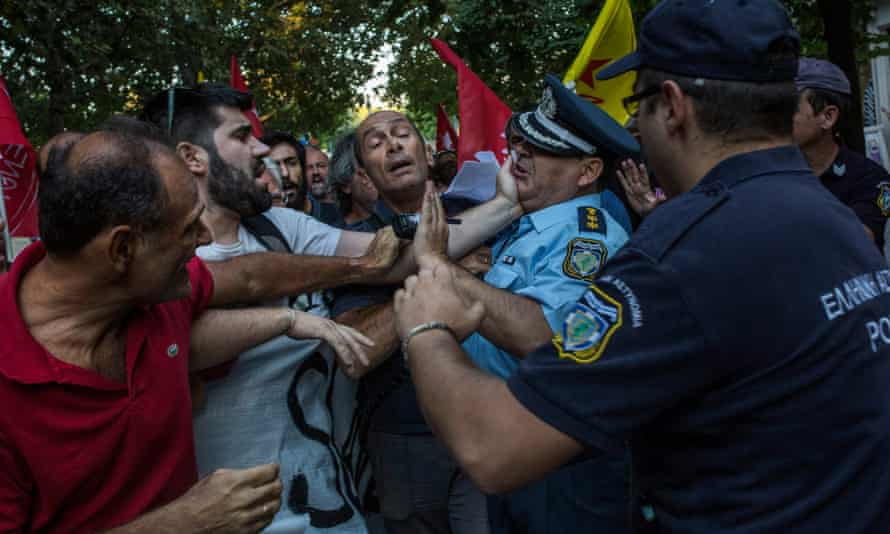 Supporters of the Popular Unity leftist party scuffle with police during a demonstration against the visit of the French president to Athens.