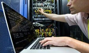 A technician checking a server in a data centre.
