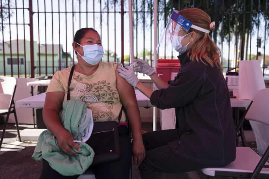 Juanita Ortega, left, receives a Covid-19 vaccine from registered nurse Anne-Marie Zamora at a pop-up vaccine clinic in Los Angeles.
