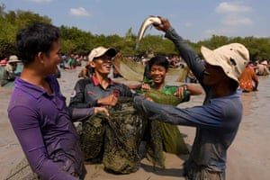 Tboung Khmum, Cambodia: A man holds up a snake fish during a ceremony at Choam Krovean commune