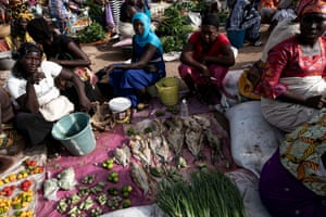 Fish and vegetable sellers wait for customers at Tanji fish market.