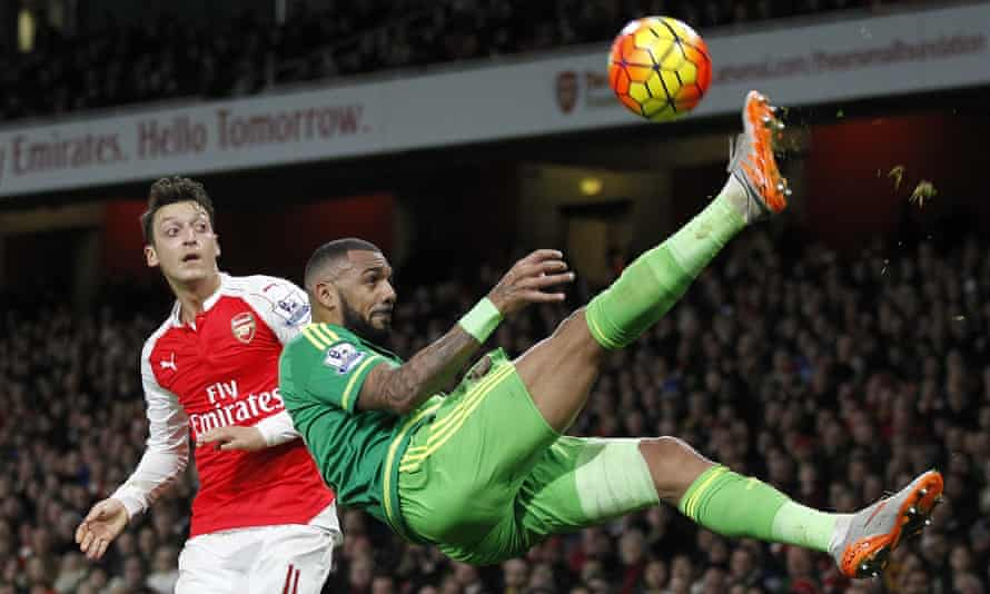 Arsenal's Mesut Özil watches as Sunderland's Yann M'Vila clears the ball in spectacular fashion.