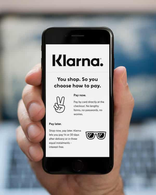 A man looks at his phone, which displays the Klarna logo