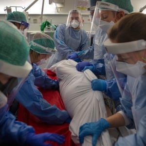 The team wrap the patient tightly in a sheet to ensure that the lines into the patient are not disturbed.