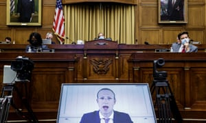 Mark Zuckerberg on a video screen facing the camera with members of a congressional committee in masks in the background
