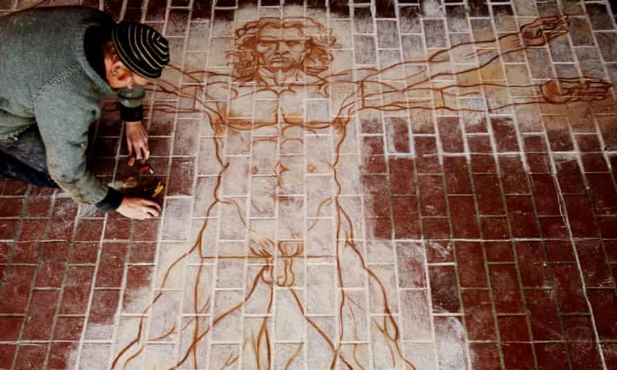 Pavement artist Jon Hicks working on a chalk drawing of Leonardo da Vinci's Vitruvian Man.