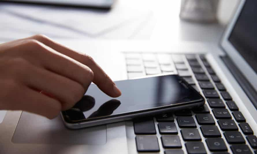 Close Up Of Person At Laptop Using Mobile PhoneEME37J Close Up Of Person At Laptop Using Mobile Phone