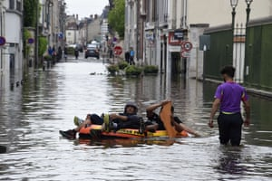 Residents float on an inflatable raft through flooded streets of Montargis