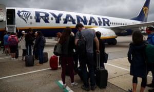 Passengers wait to board a Ryanair flight